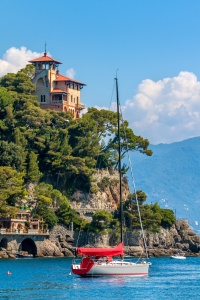 Yacht on the sea and beautiful pld villa on the cliff in Portofino, Italy (vertical composition).